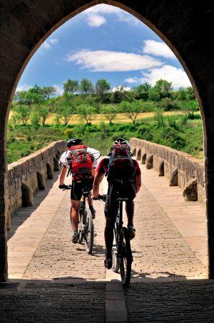 Dois ciclistas na ponte românica de Puente la Reina, na passagem do Caminho de Santiago por Navarra.