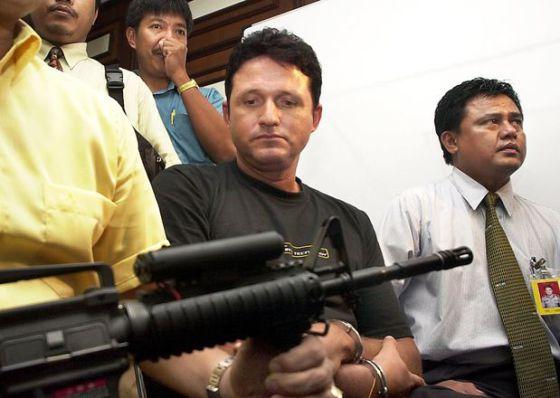 Polícia acompanha brasileiro Marco Archer Cardoso Moreira durante uma coletiva de imprensa em Jakarta, em 2003.
