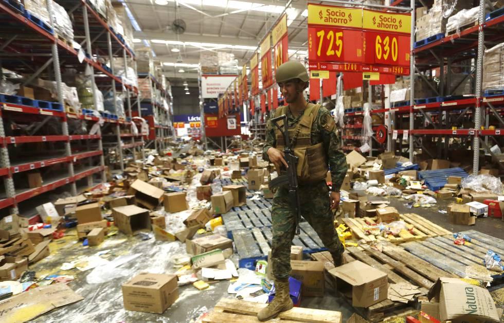 Soldado chileno monta guarda num supermercado afetado por saques, em 22 de outubro.