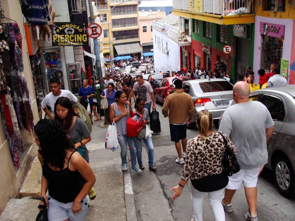 Pedestres e carros em uma rua comercial de São Paulo.