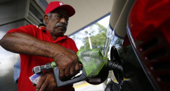 Um homem enche o tanque de combustível em Caracas.