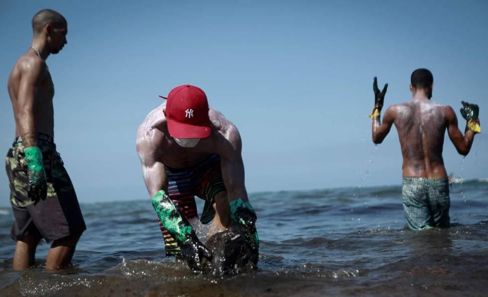 Voluntários retiram óleo na praia de Itapuama, na cidade de Cabo de Santo Agostinho, Pernambuco.
