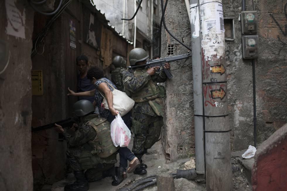Mulher desliza entre soldados para ultrapassar uma barreira armada em um beco da Rocinha.