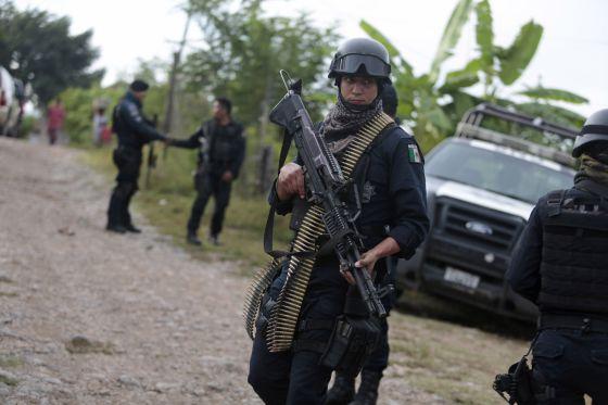 Um policial mexicano nas redondezas das valas de Iguala.