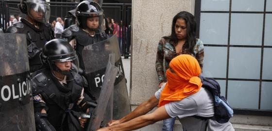 Manifestante enfrenta a polícia em Caracas.
