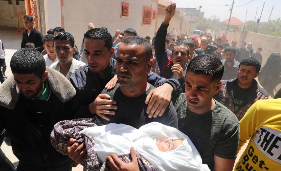Pai de menina morta por um projétil leva a filha para o funeral, neste domingo, em Gaza.
