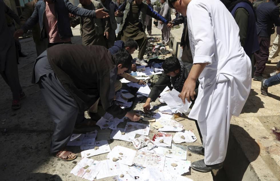 Afegãos recolhem documentos e fotos das pessoas mortas e feridas no atentado deste domingo em Cabul.