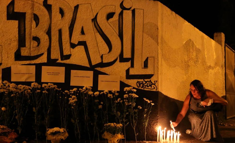 Mulher acende vela em tributo a vítimas do ataque em Suzano.