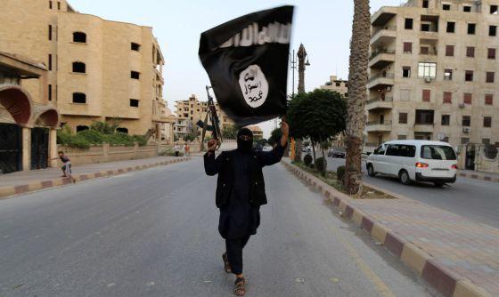 Miliciano com uma bandeira do EI em Raqqa (Síria).