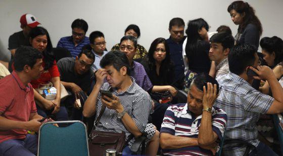 Familiares dos passageiros esperam notícias no aeroporto de Surabaya.