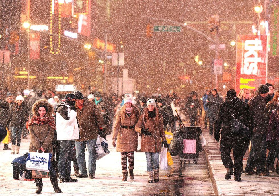 Pessoas passeiam sob a neve na Broadway, em Nova York.
