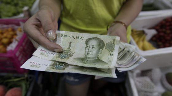 Vendedora mostra notas de yuan em Pequim.