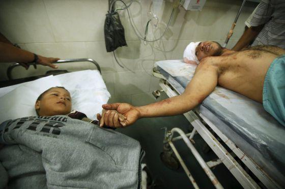 Um pai e um filho hospitalizados depois dos bombardeios israelenses em Gaza.