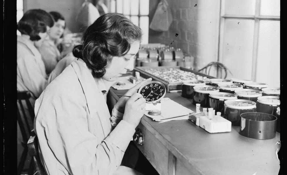 Uma trabalhadora emprega pintura luminosa em uma fábrica de relógios em 1932.