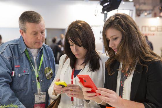 Duas mulheres verificam celulares no Mobile World Congress.
