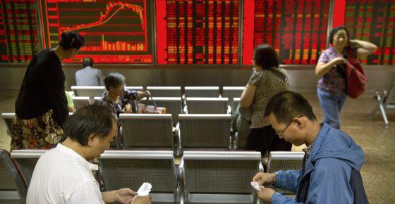 Muitos investidores acompanham as cotações em um painel da Bolsa de Pequim, que tem alta volatilidade.