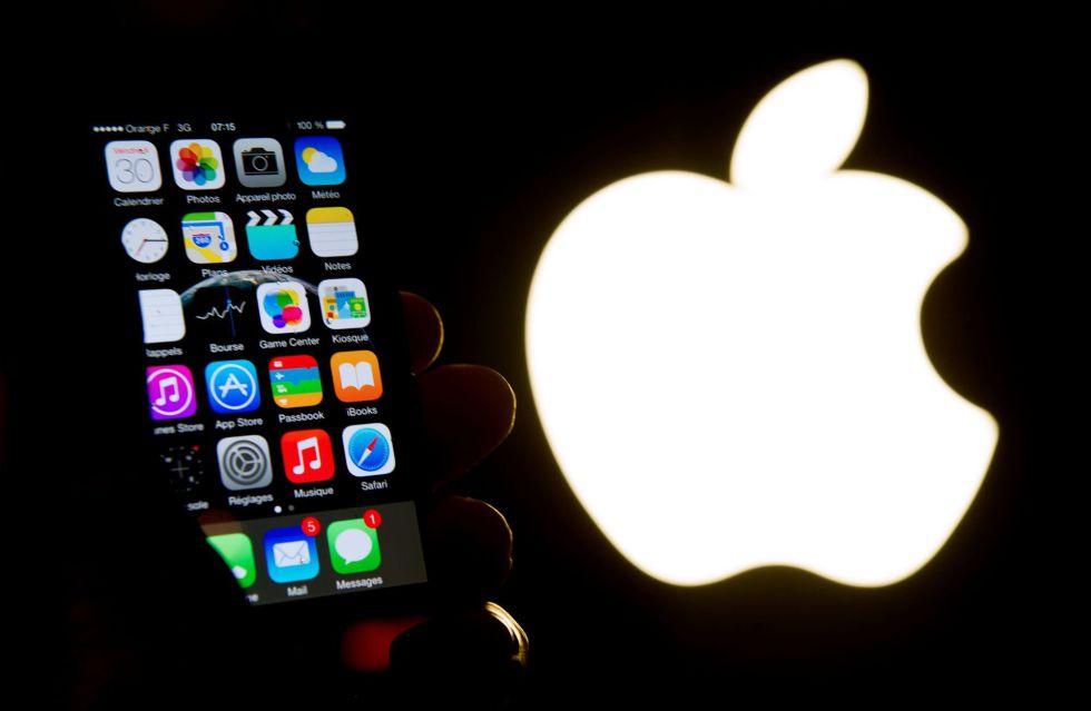 Um telefone Apple e o logotipo da companhia / AFP / PHILIPPE HUGUEN
