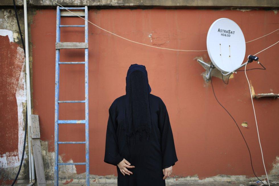 De preto dos pés à cabeça, uma mulher libanesa de 32 anos posa no teto de sua casa em Beirute, a capital do Líbano. Seu pai é xiita e sua mãe é sunita. Ela usa o 'nicabe', peça de roupa que esconde o rosto e deixa descobertos apenas os olhos. Estes, por sua vez, podem ser cobertos por um fino véu quase transparente. Normalmente, elas também usam o resto do corpo coberto. Nas imagens seguintes o mundo é mostrado através do nicabe, com a falta de nitidez como as mulheres a enxergam