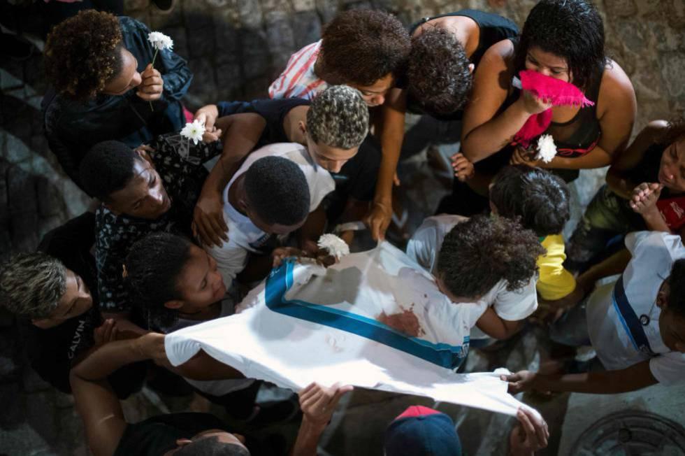 Amigos e familiares de Marcos Vinícios choram sobre sua camiseta da escola manchada de sangue, durante o seu velório.