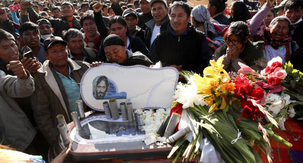 Uma multidão cerca o caixão de uma das vítimas durante os protestos na Bolívia.