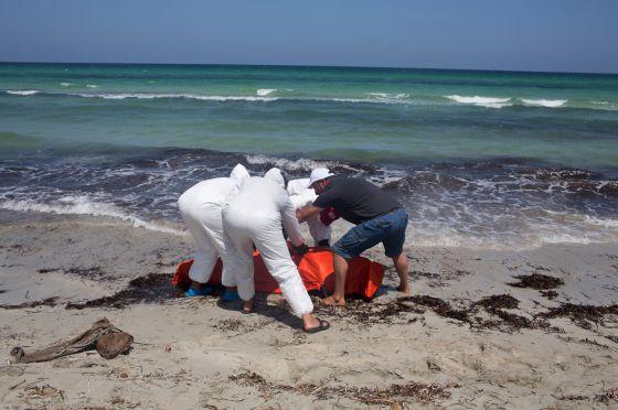 Trabalhadores transladam cadáver de imigrante afogado em frente à costa líbia.