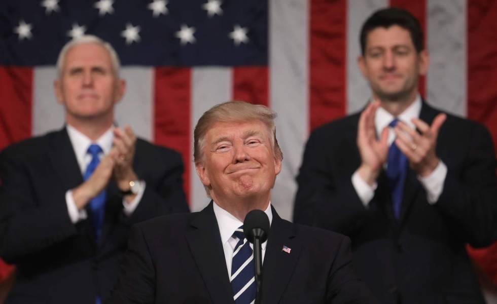 O presidente Trump sorri na presença do seu vice, Mike Pence, e do presidente da Câmara de Deputados, Paul Ryan.