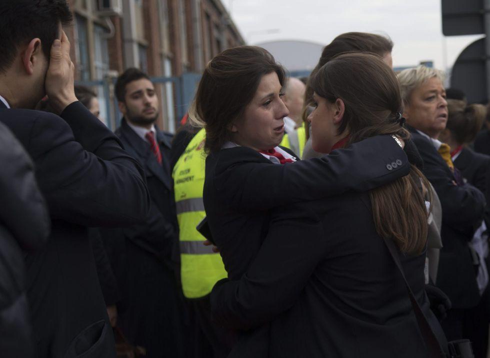 Trabalhadores do aeroporto de Bruxelas se abraçam depois dos atentados.