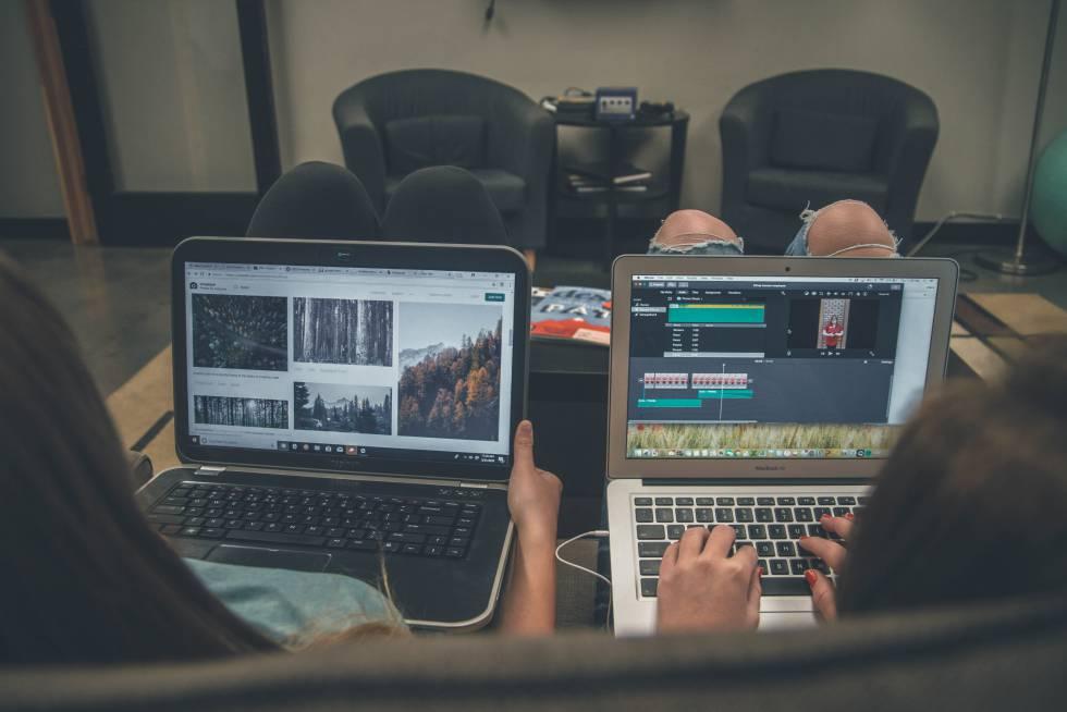 Duas pessoas navegam na internet em seus computadores