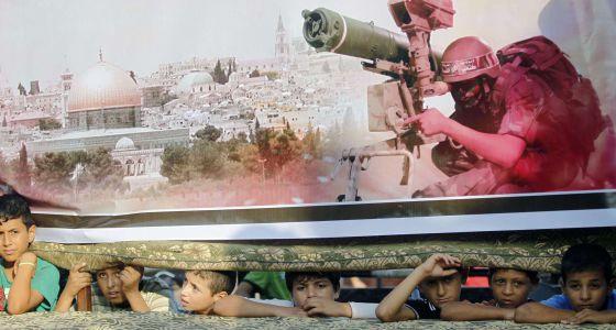 Garotos em Rafah debaixo de um cartaz do Hamas.