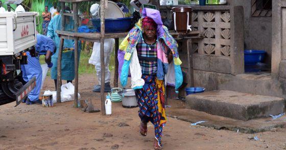 Uma mulher carrega os pertences de seu esposo, vítima do ebola, na Libéria.