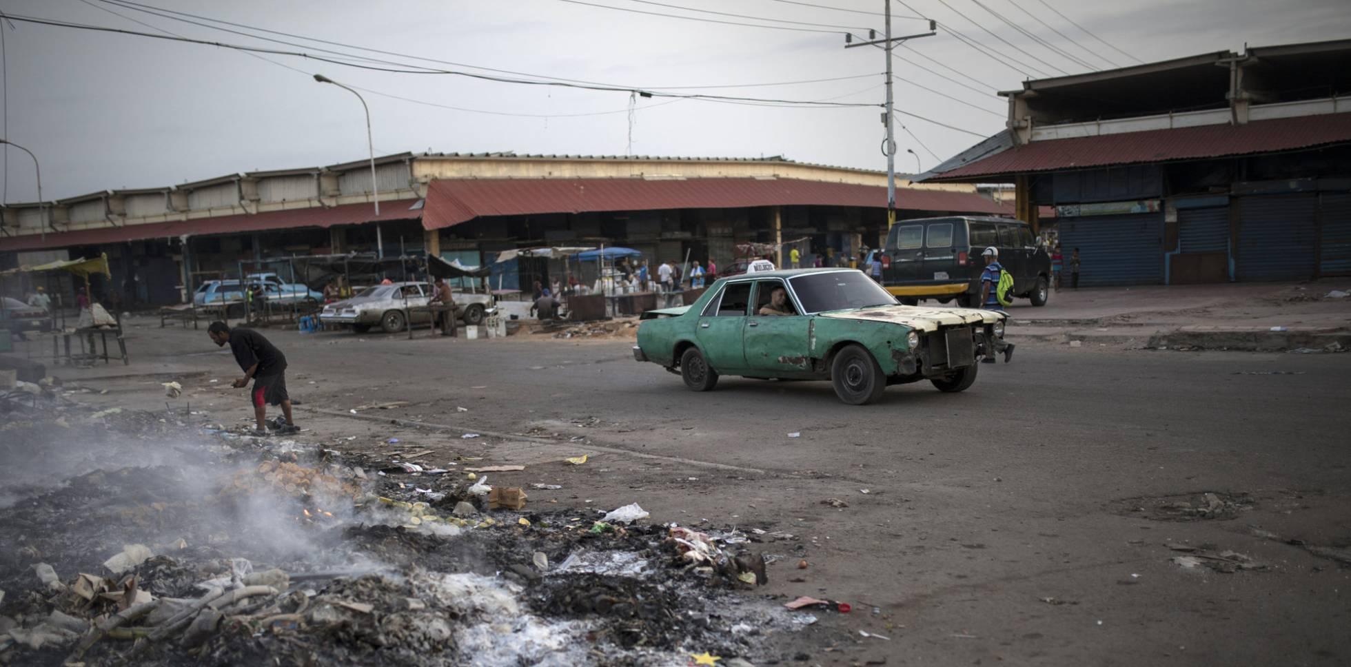 Um homem busca restos entre o lixo, em Maracaibo (Venezuela).