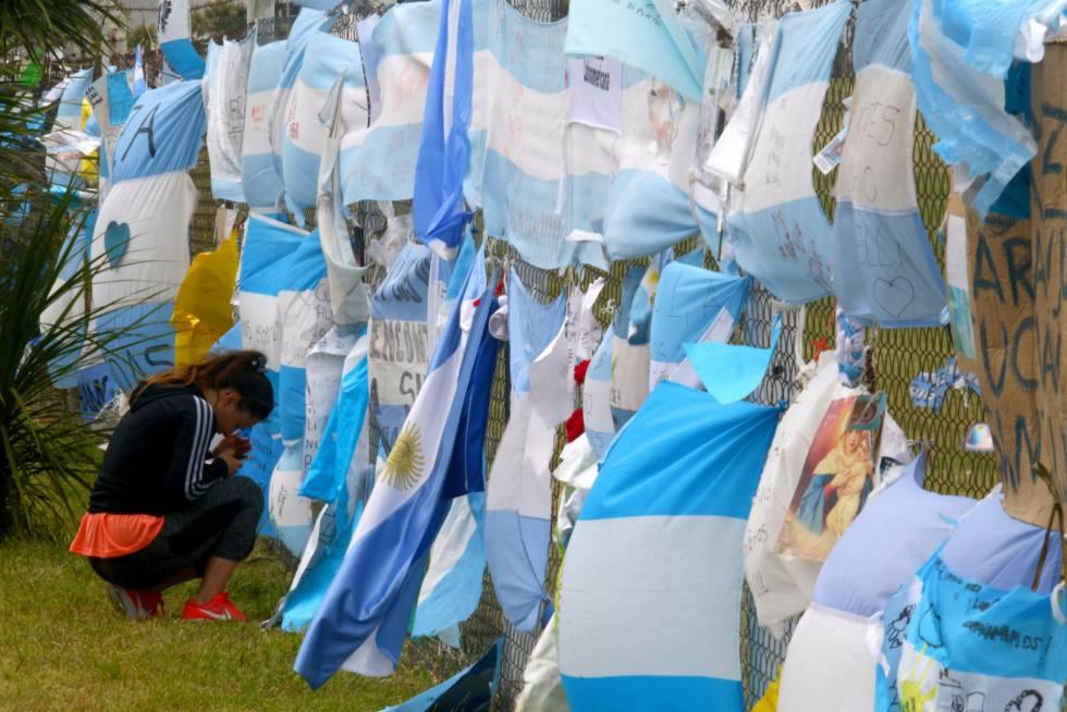 Mulher se ajoelha ante as bandeiras que homenageiam os 44 tripulantes do Ara San Juan, na base naval de Mar da Prata.