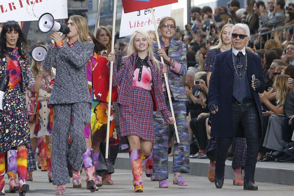 """O estilista Karl Lagerfeld não teme polêmica e fechou seu desfile de primavera/verão 2015 para Chanel com uma manifestação. Lideradas por Cara Delevigne com um megafone, os modelos portavam cartazes em que se liam frases como """"Seja teu próprio estilista"""", """"As mulheres primeiro"""" ou """"Liberemos a liberdade""""."""