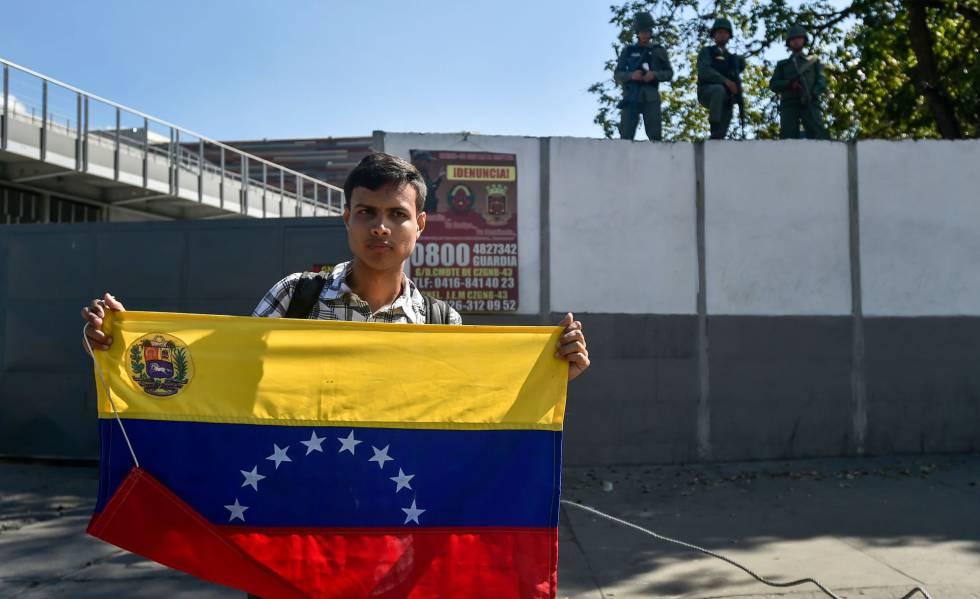 Venezuelano com a bandeira do país em frente a um quartel