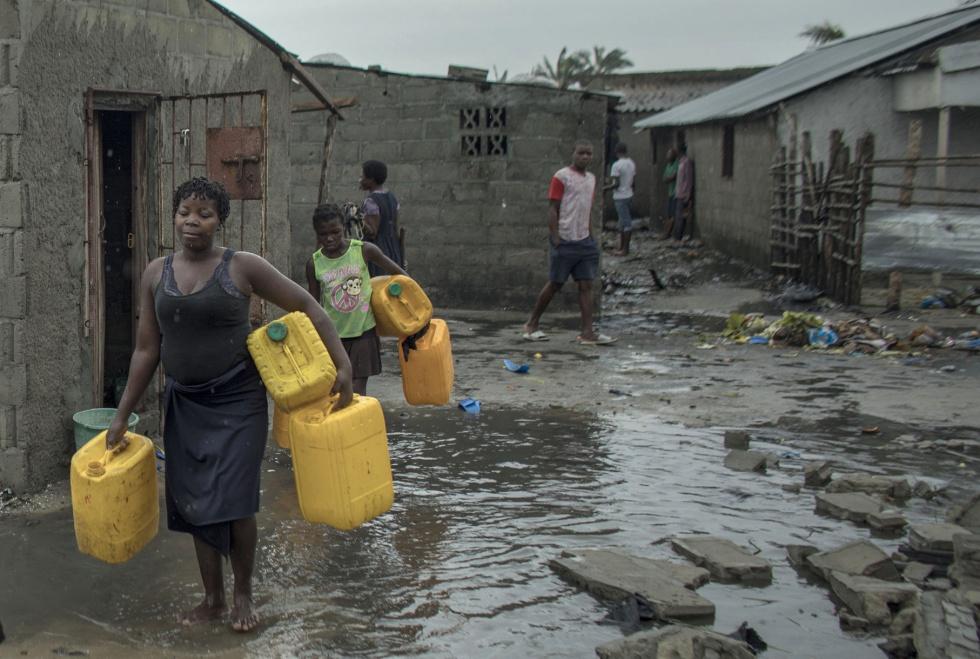 Várias pessoas carregam latas para procurar água em Praia Nova Village, um bairro de Beira, Moçambique.
