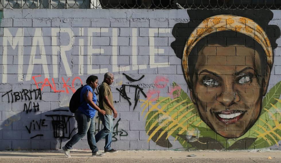Dois transeúntes ante um grafiti de Marielle Franco, o vereador assassinada faz em um ano em Rio.