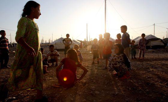 Crianças refugiadas brincam no campo de Baharka.