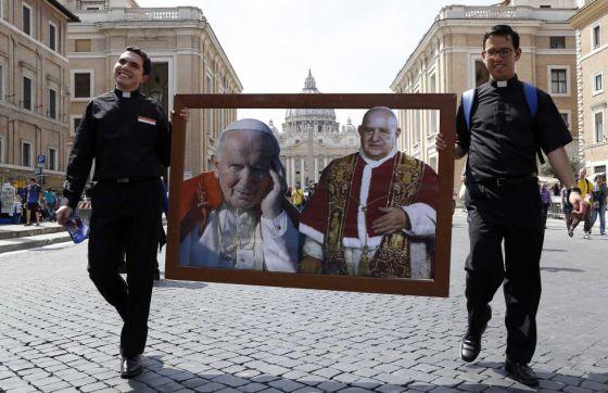 Dois sacerdotes caminham pela Praça de San Pedro com um quadro com os dois papas que serão canonizados no próximo dia 27.