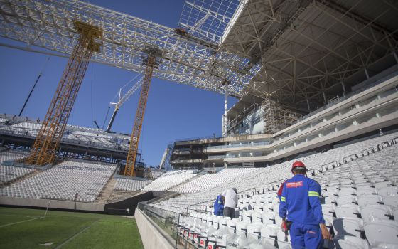 Operários trabalham na construção da Arena Corinthians.