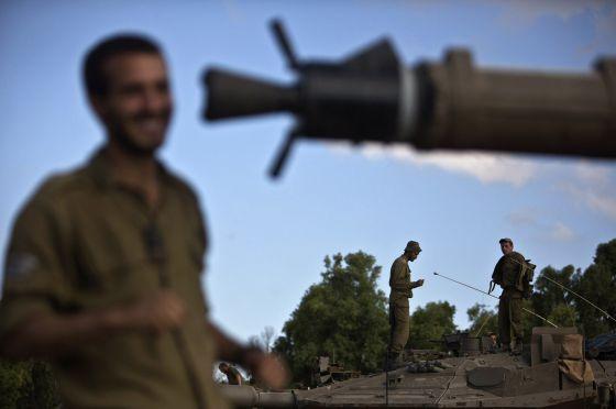 Soldados israelenses sobre um tanque na fronteira com Gaza.