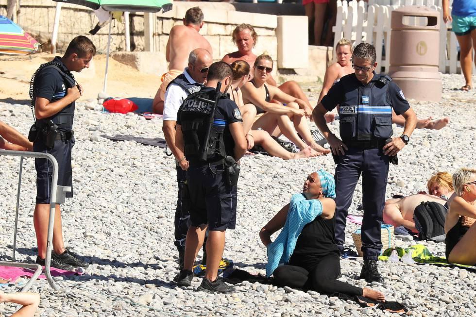 Uma mulher tira a camisa, enquanto a polícia aplica uma multa em Nice.