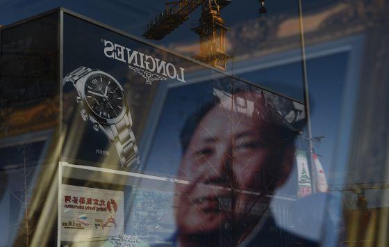 Propaganda reflete em vitrine que expõe foto de Mao Tsé-Tung.