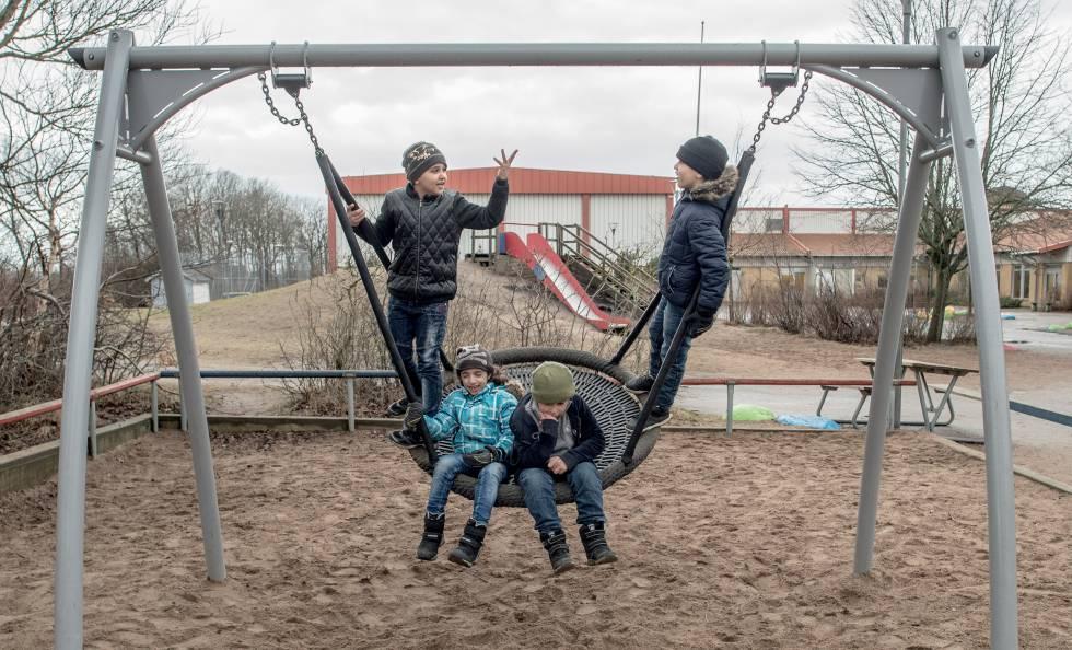 Crianças refugiadas, na balança do pátio de um colégio em Halmstad, Suécia.