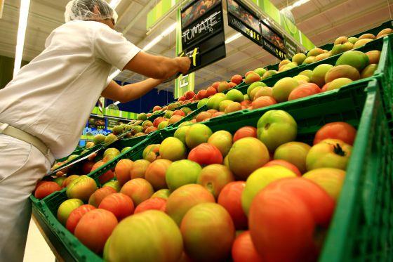 Funcionário corrige o preço do tomate em um supermercado.