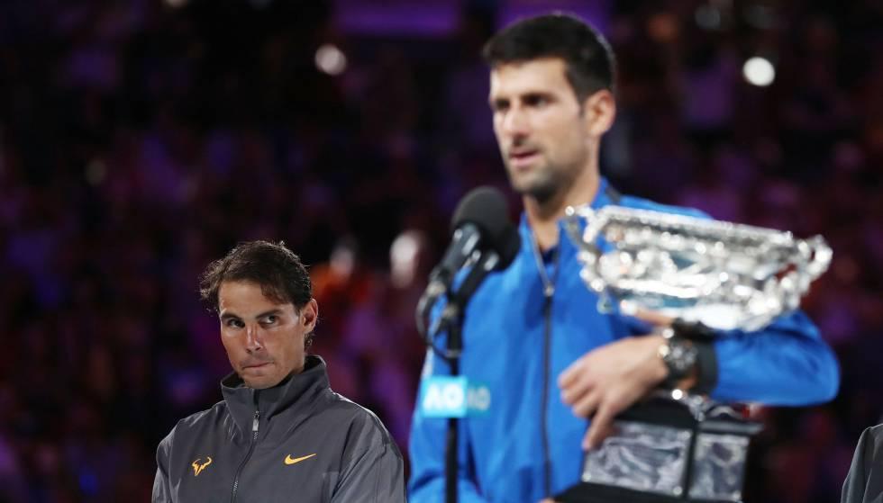 Nadal observa Djokovic durante a cerimônia de premiação em Melbourne.