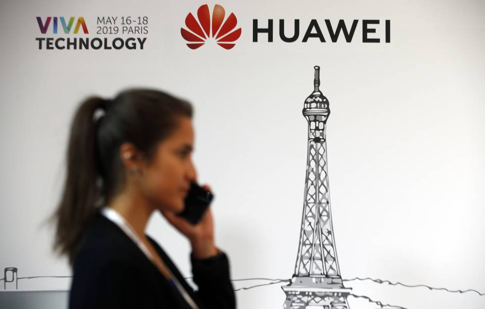 Uma mulher passa em frente a um logotipo da Huawei, neste domingo em Paris.