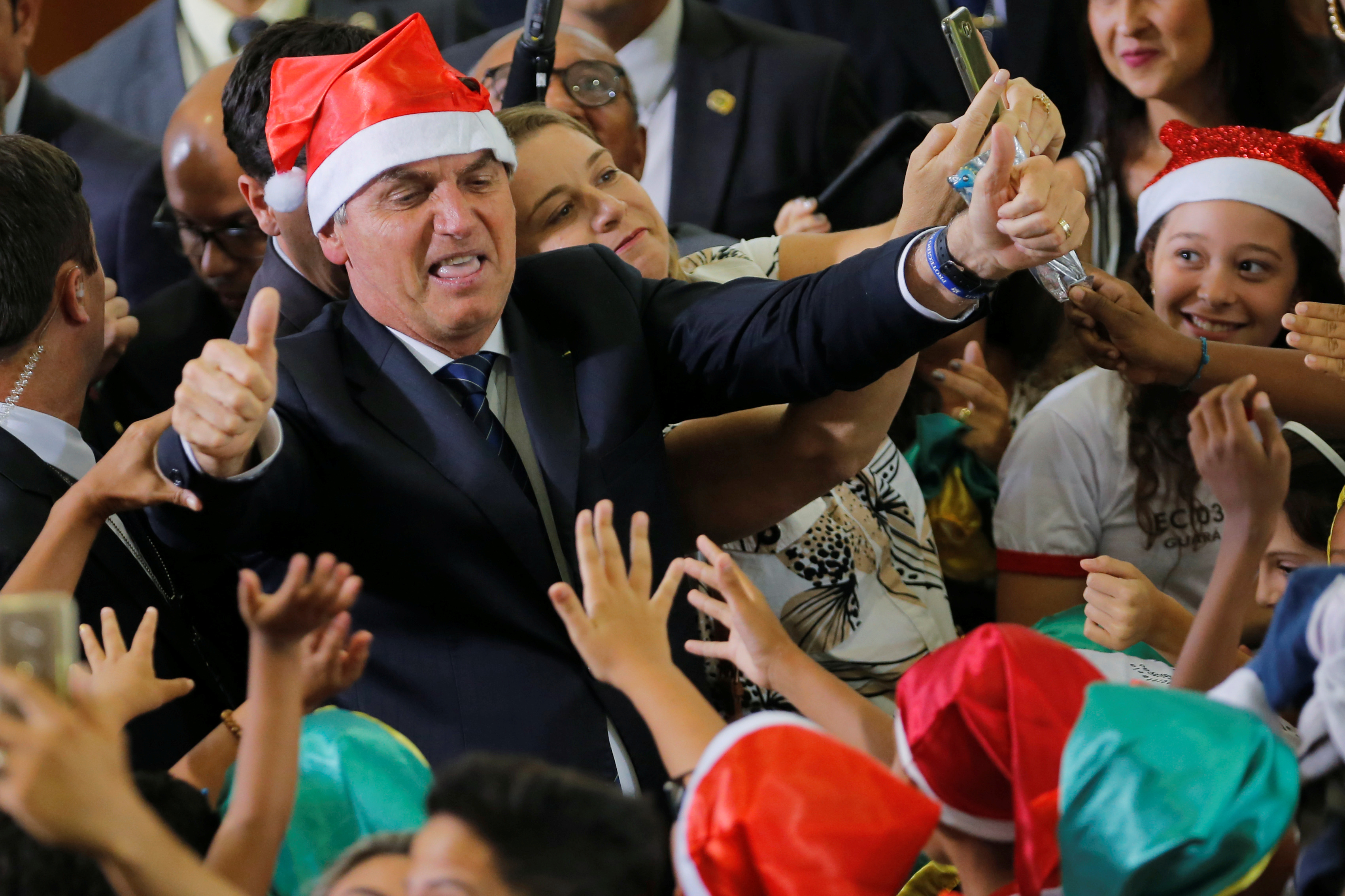 Brazil's President Jair Bolsonaro poses for a  picture wearing a Santa Claus hat during  a Christmas ceremony at Planalto Palace in Brasilia, Brazil December 19, 2019. REUTERS/Adriano Machado