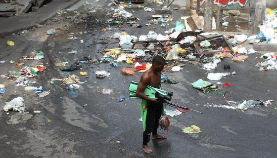 Um homem caminha por uma rua suja de Copacabana.