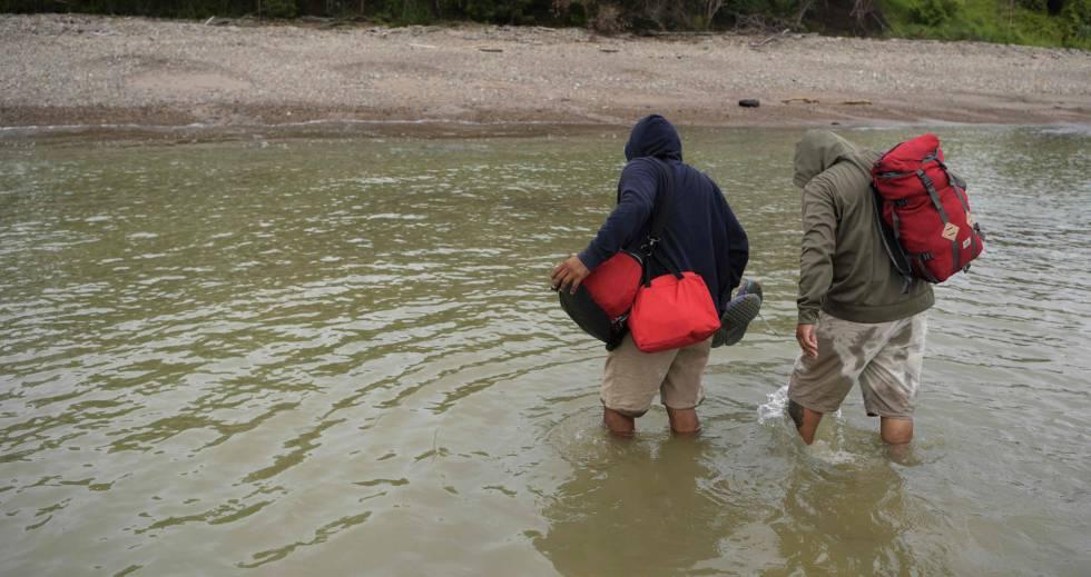 Dois homens cruzam o rio San Juan que divide a Nicarágua e a Costa Rica.