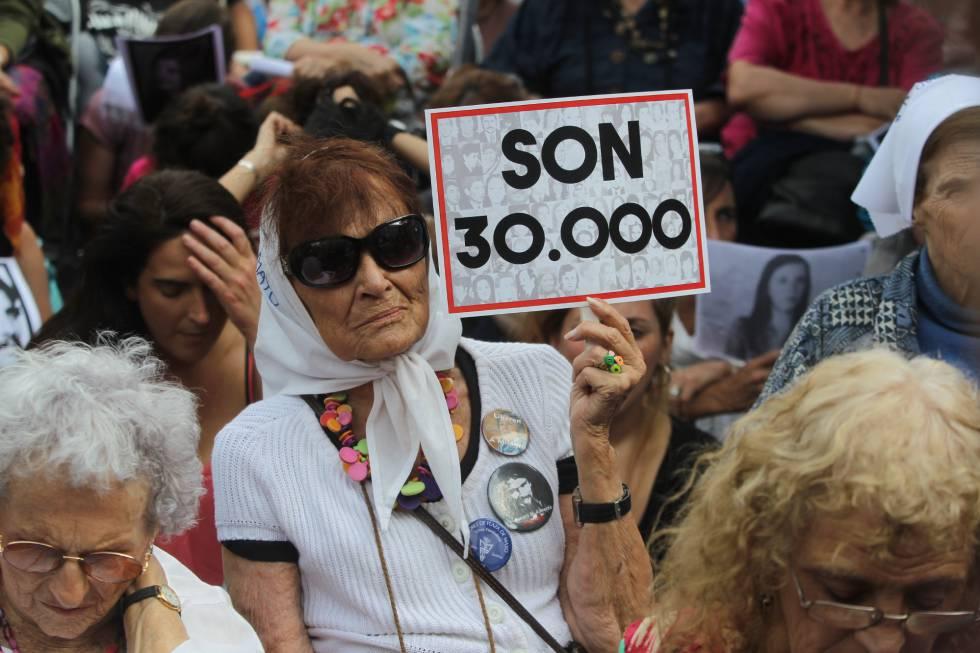 Uma mulher segura um pôster que faz referência aos 30.000 desaparecidos enquanto escuta a leitura do veredicto pelos crimes cometidos na Escola de Mecânica da Armada (ESMA).